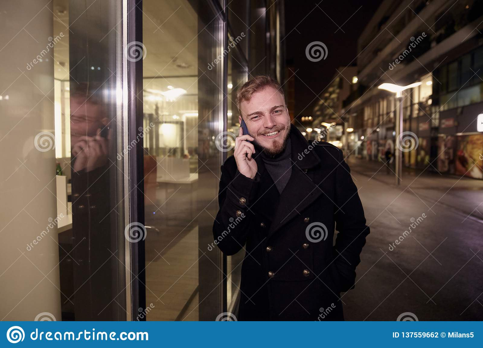 Night time, one young smiling and happy man, 20-29 years, talking over his phone, standing in Autumn coat on street, in front of