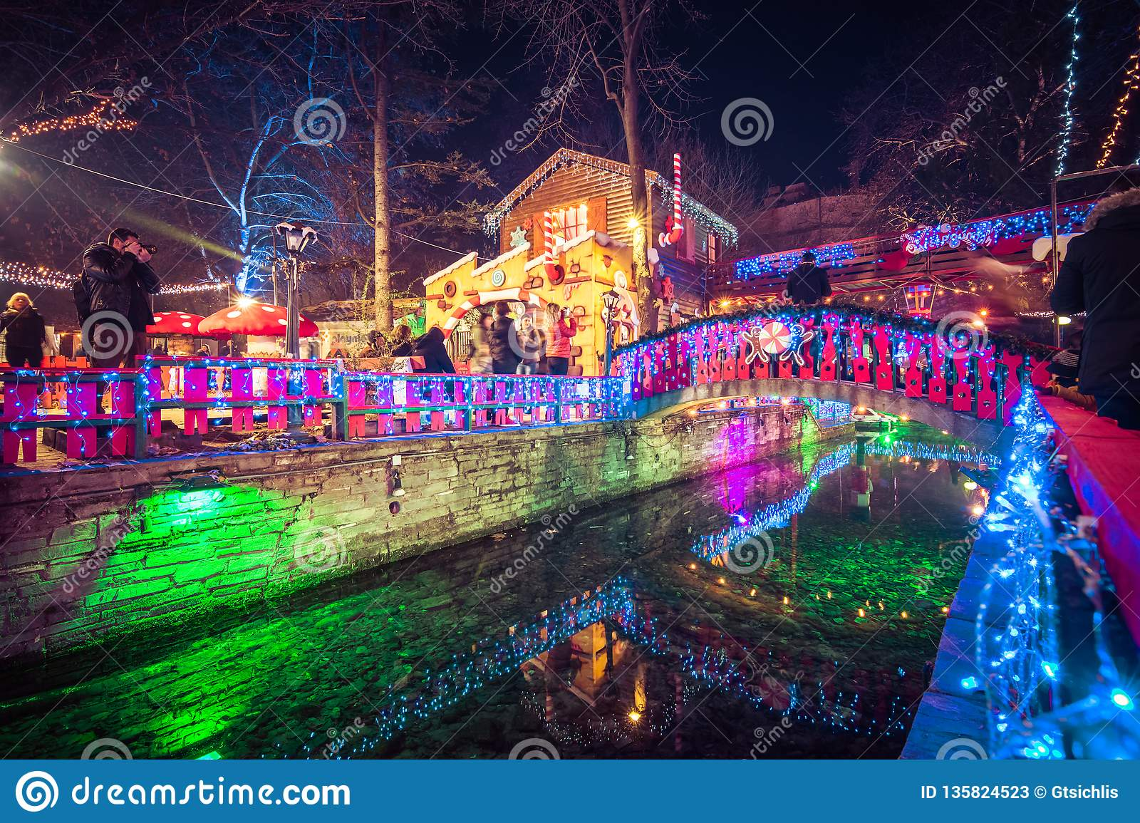 """Night View Of The Greek Christmas Market """"Oneiroupoli"""" With Lights, Figurines Around The River ..."""