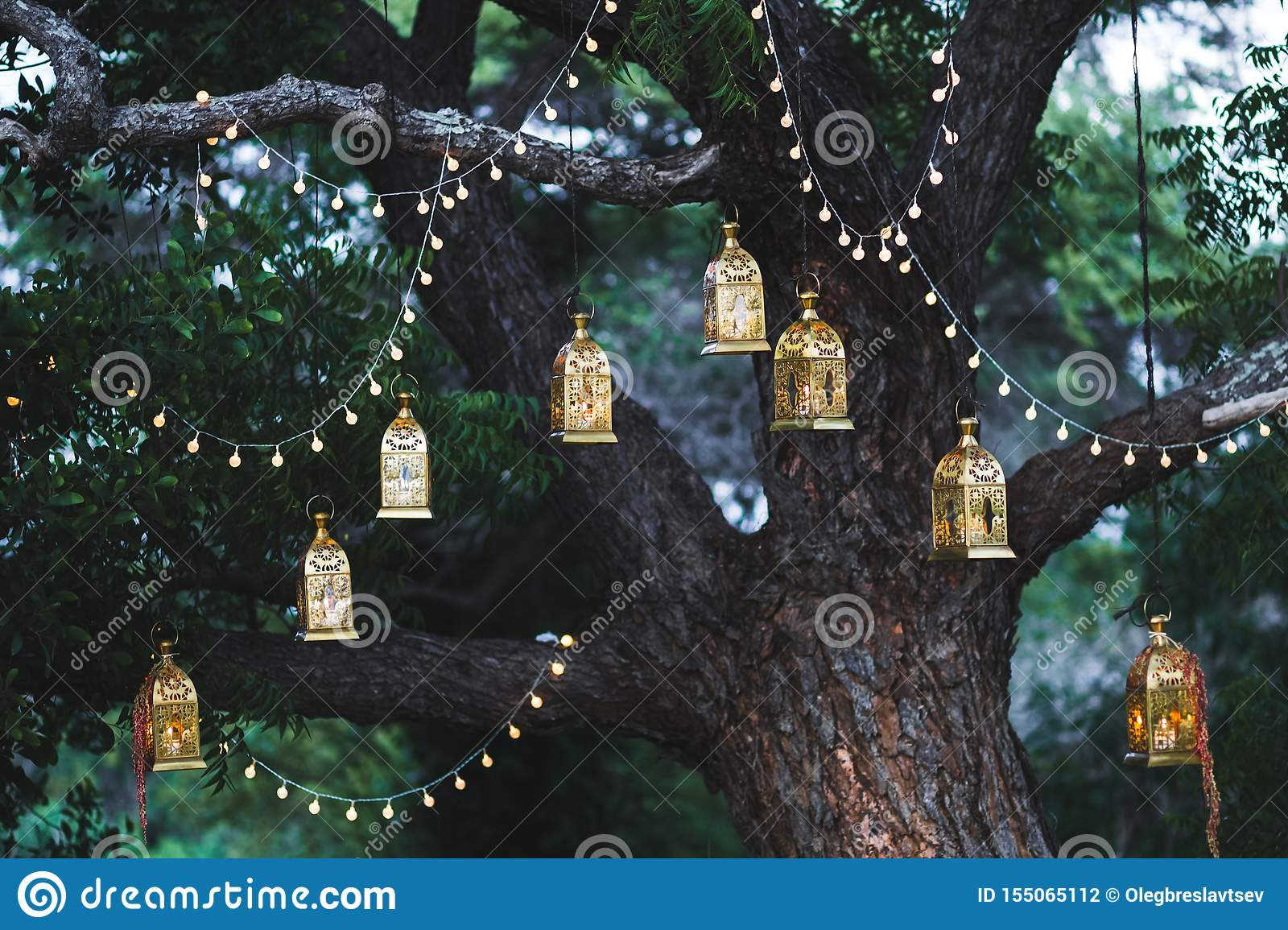 Night wedding ceremony with vintage lamps on tree