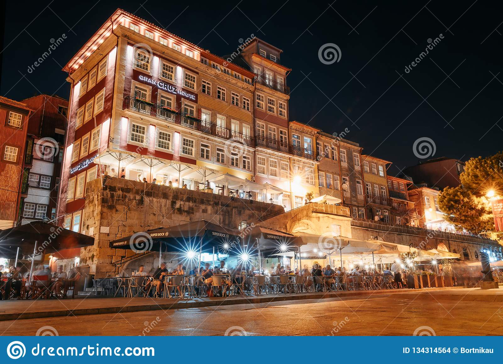 Nightlife on the crowded promenade of the Douro River with cafes and restaurants in Porto