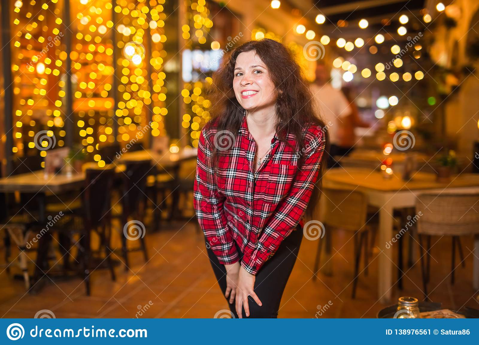 Nightlife, party and lifestyle concept - Girl walking in night city stock image