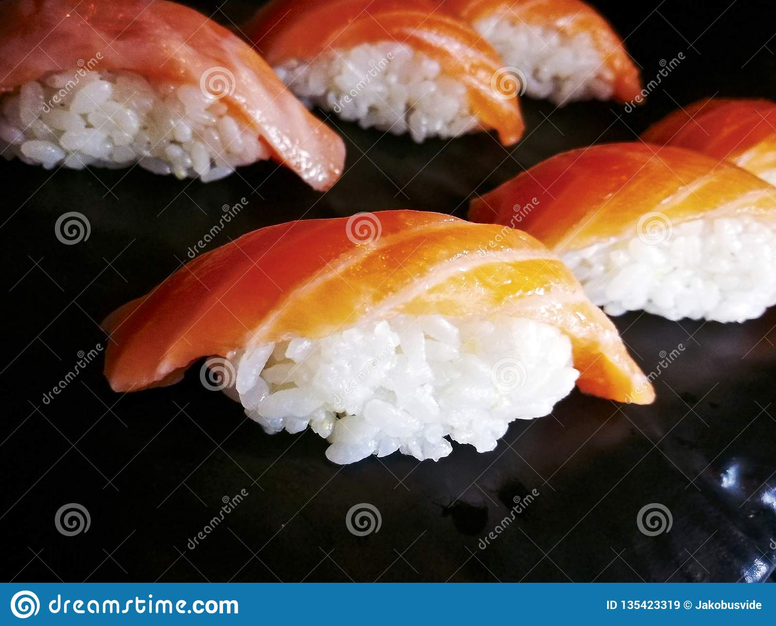 Nigiri缘故三文鱼寿司关闭在一个黑盘