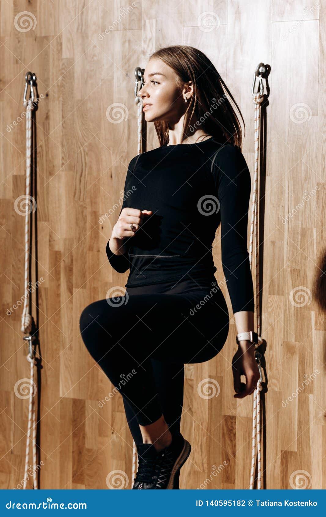 Nikła dziewczyna ubierająca w czarnym sportswear skacze obok linowego wyposażenia w nowożytnym gym z drewnianym