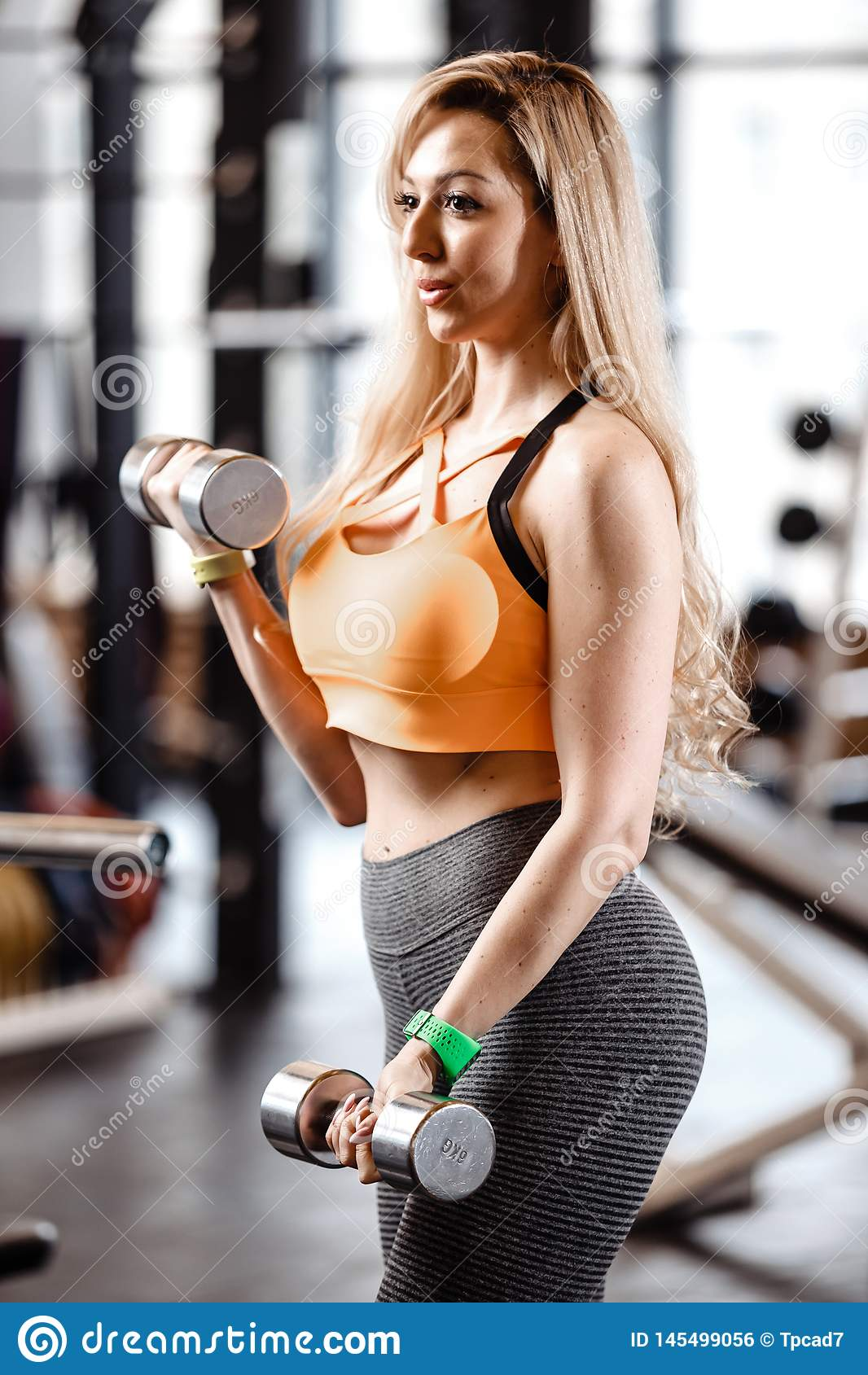 Nikła blond dziewczyna z długie włosy ubierającym w sportswear robi ćwiczeniom z dumbbells w nowożytnym gym z dużym