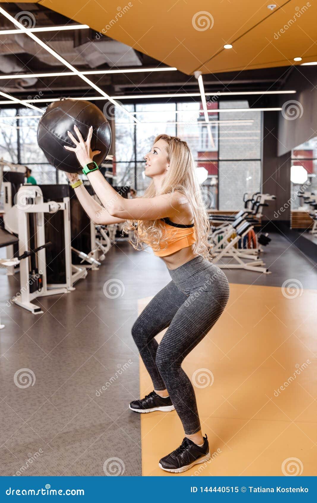 Nikła blond dziewczyna z długie włosy ubierającym w sportswear robi z powrotem kuca z ciężką sprawności fizycznej piłką w nowożyt
