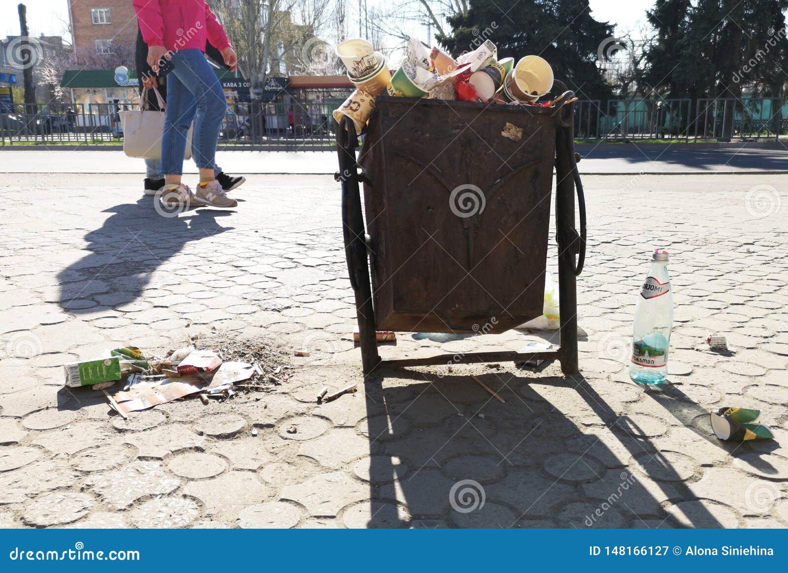Nikopol, Ukraina, Maj 20, 2019: zat?oczony kube? na ?mieci na Ukrai?skiej ulicie z ?mieci na brukowych cegie?kach,