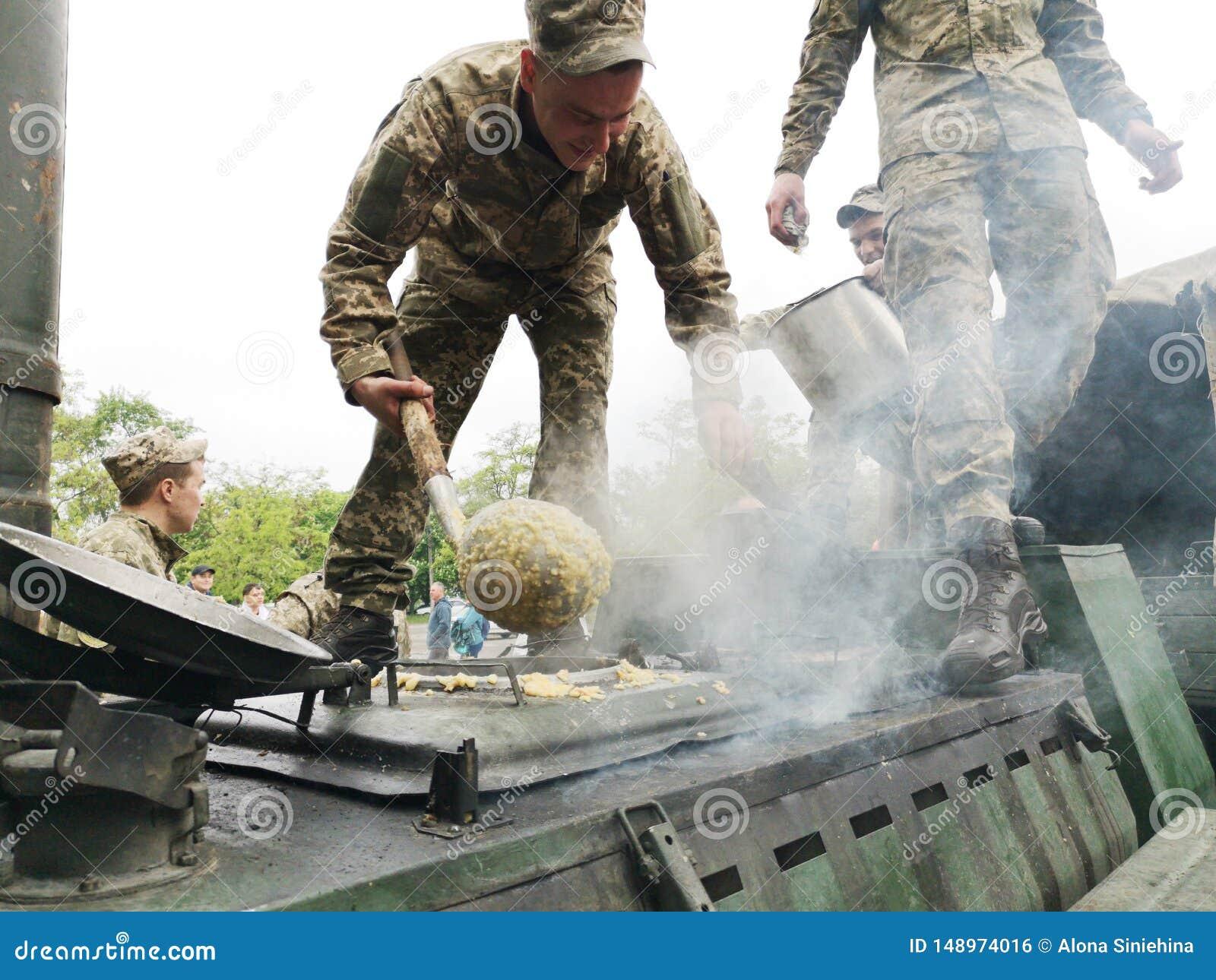 NIKOPOL, UKRAINE - MAI 2019: Ukrainisches Milit?r kocht den Brei der Soldaten und behandelt Leute zu ihm an der Parade zu Ehren