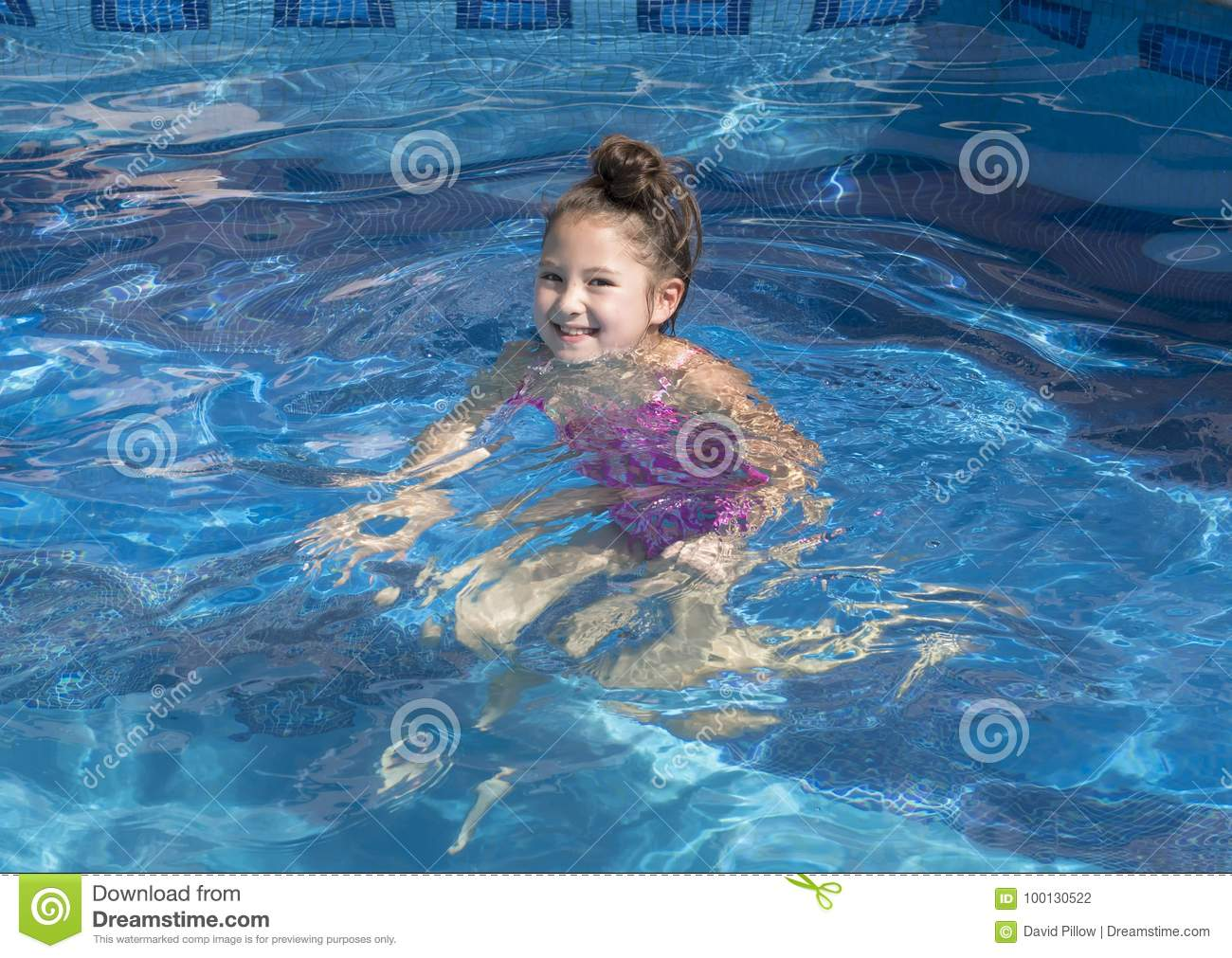 Nine year-old girl treading water in a swimming pool