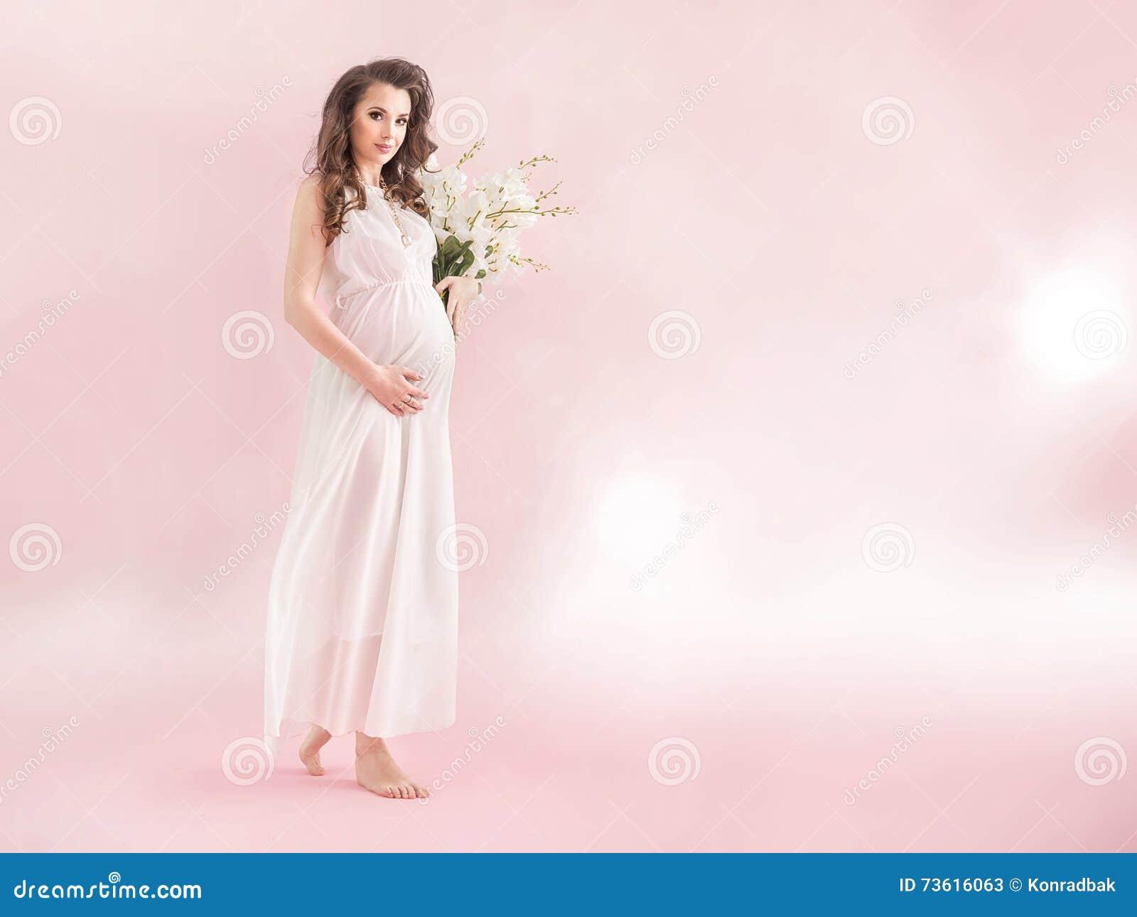 Ninfa grávida dos jovens que guarda um ramalhete do wildflowers