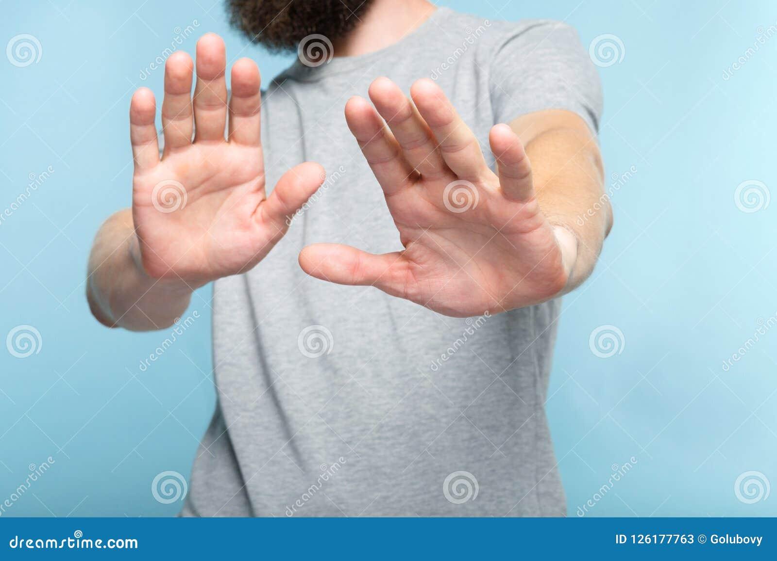 Ningunas palmas de las manos del hombre de la denegación del rechazo empujan lejos
