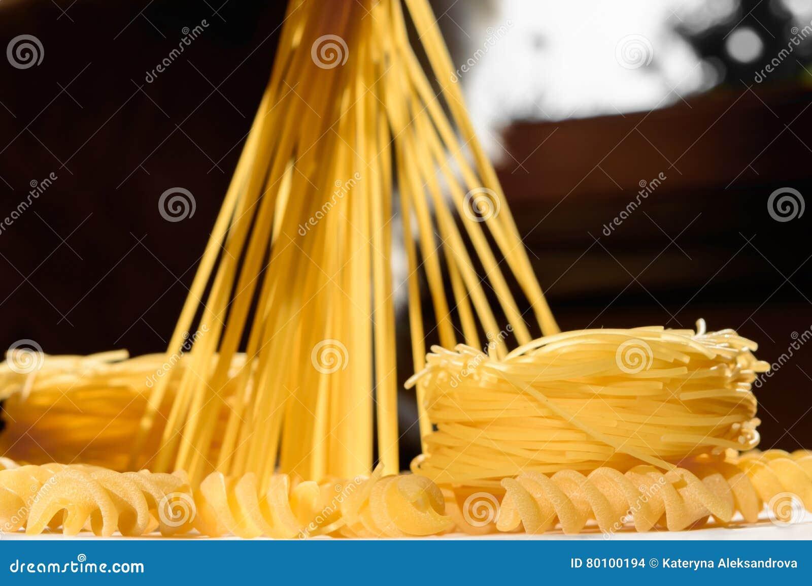 Ninhos e suporte da massa dos espaguetes eretos em uma cozinha iluminada