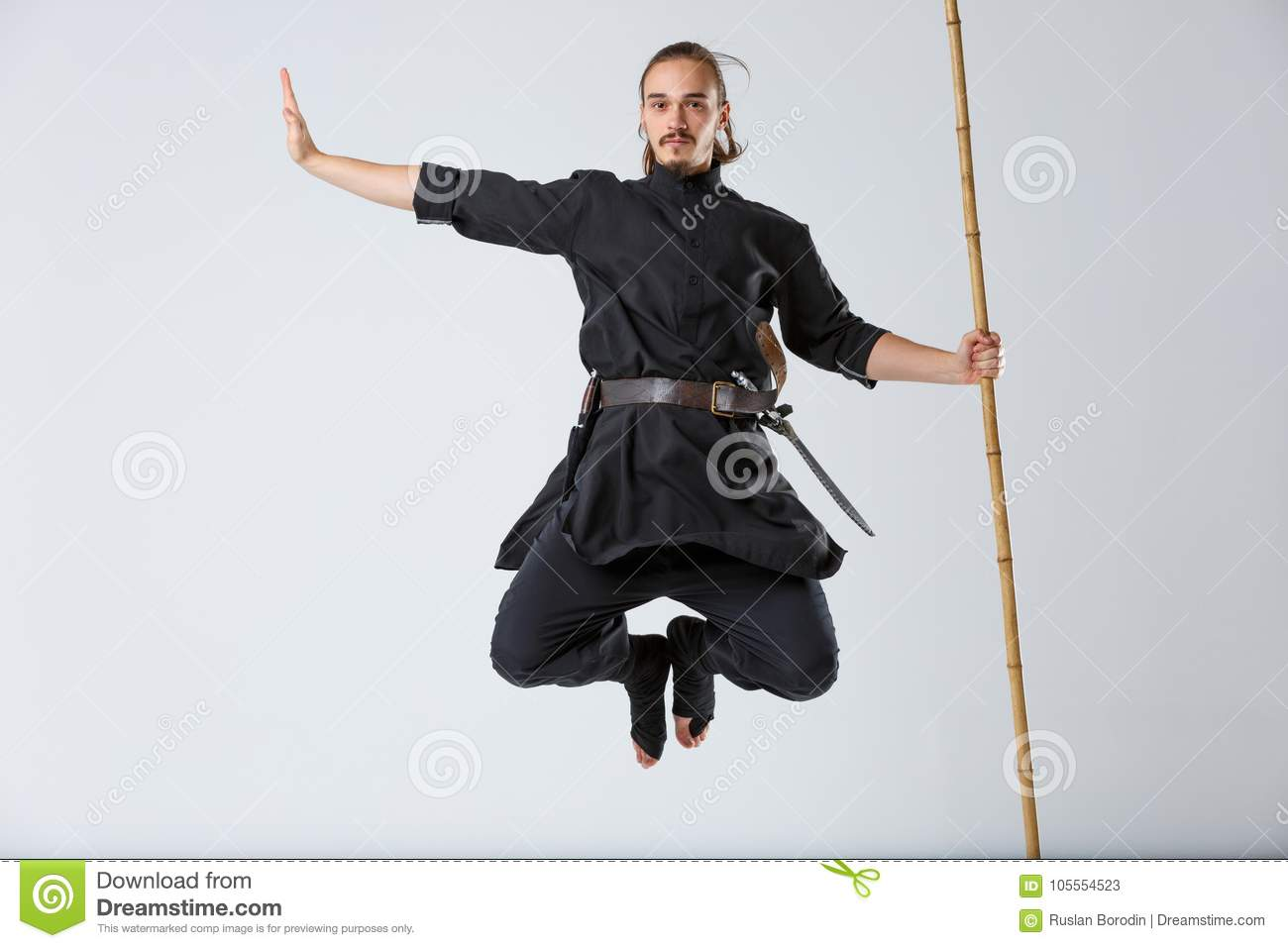 A ninja man in a jump holds a battle stick vertically on a gray background