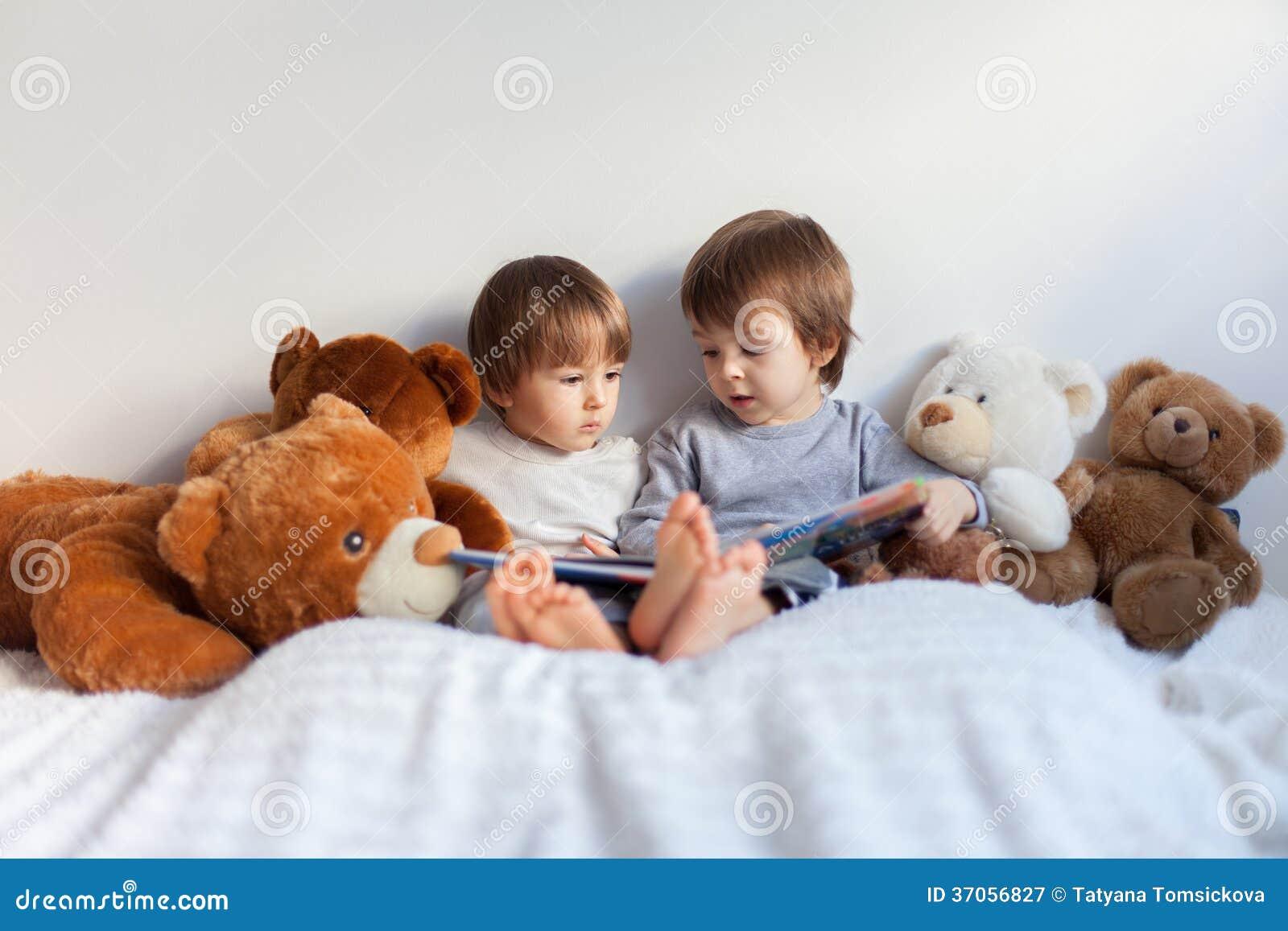 Ni os peque os sent ndose en la cama leyendo un libro - Cama para ninos pequenos ...