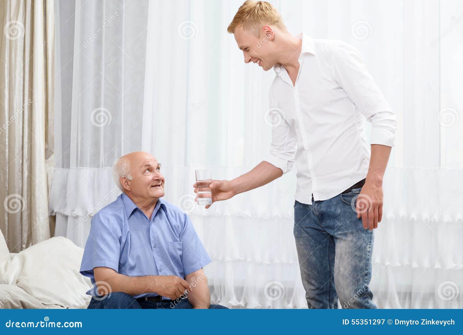 Nipote che dà vetro con acqua al nonno