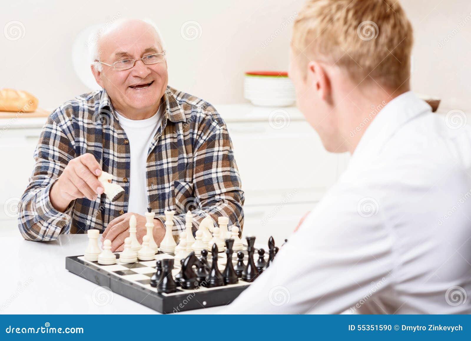 Nipote e nonno che giocano scacchi in cucina