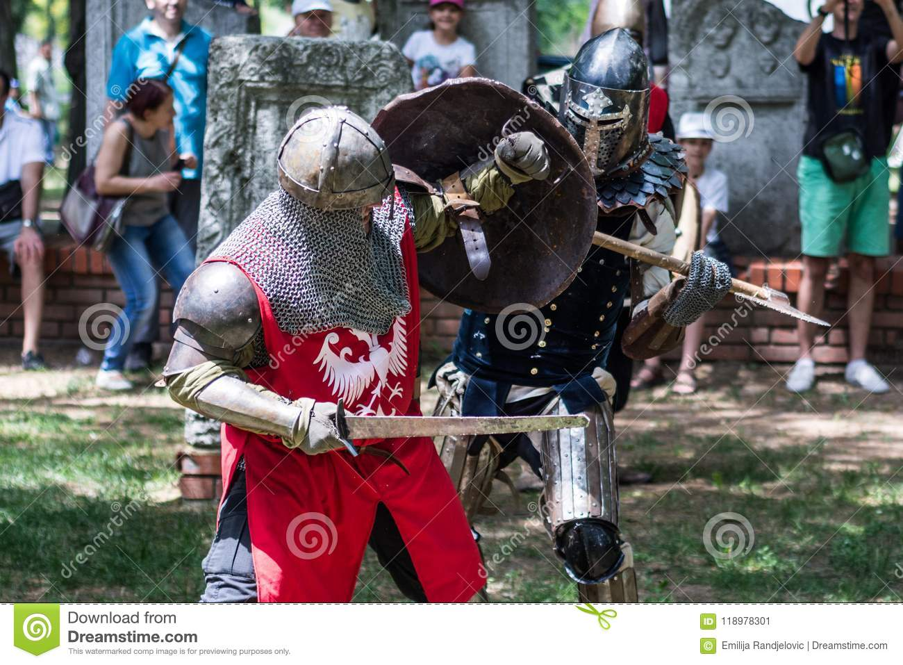 Two medieval knights fighting with hard weapon in armor in nature