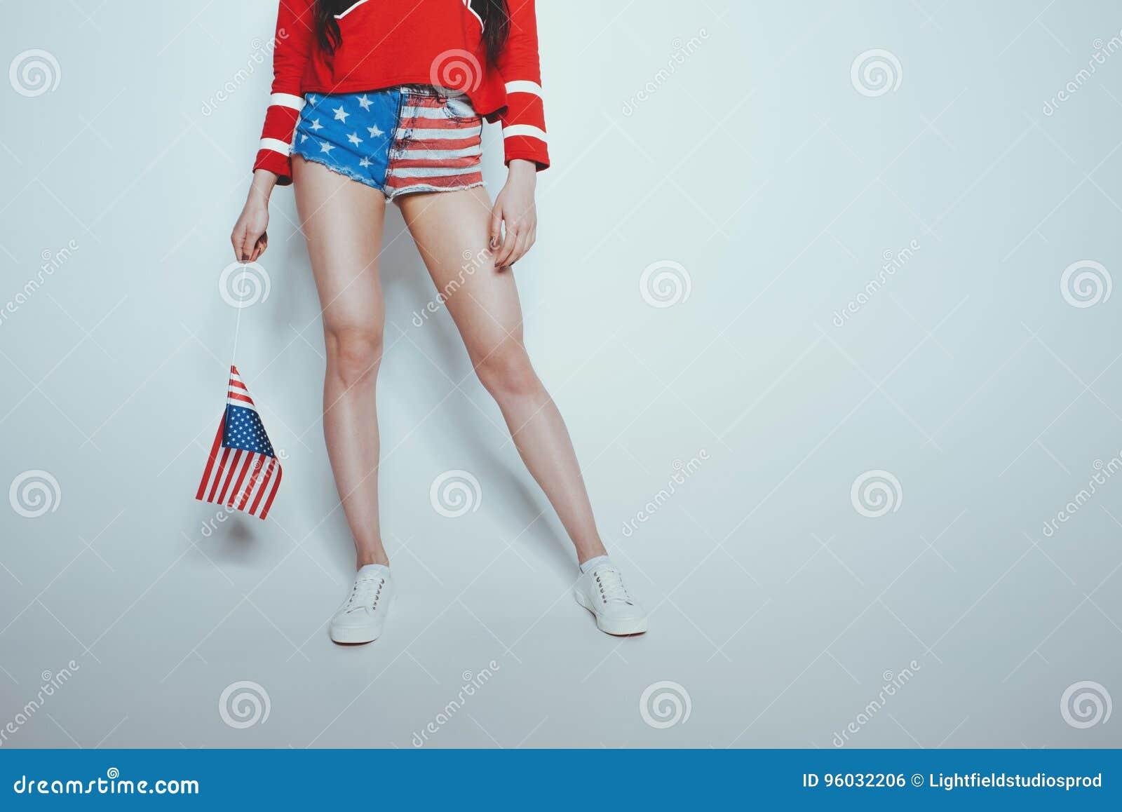 Niska sekcja elegancka modniś dziewczyna w amerykańskim patriotycznym stroju odizolowywającym na popielatym