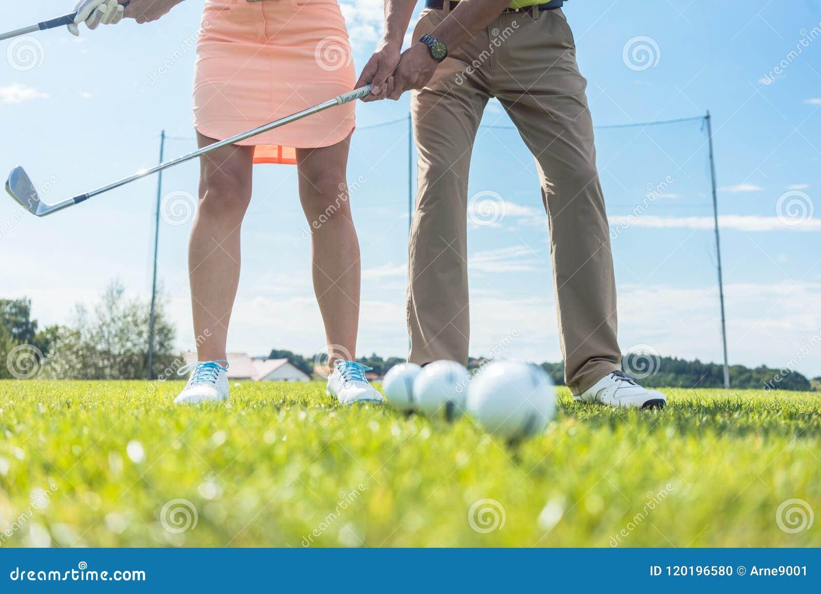 Niska sekcja mężczyzna i kobiety mienia żelaza kluby podczas gdy ćwiczyć