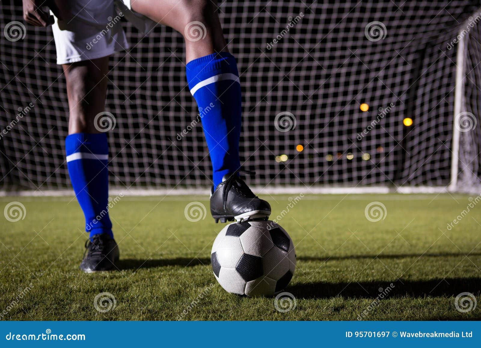 Niska sekcja męska gracz piłki nożnej pozycja z piłką na polu