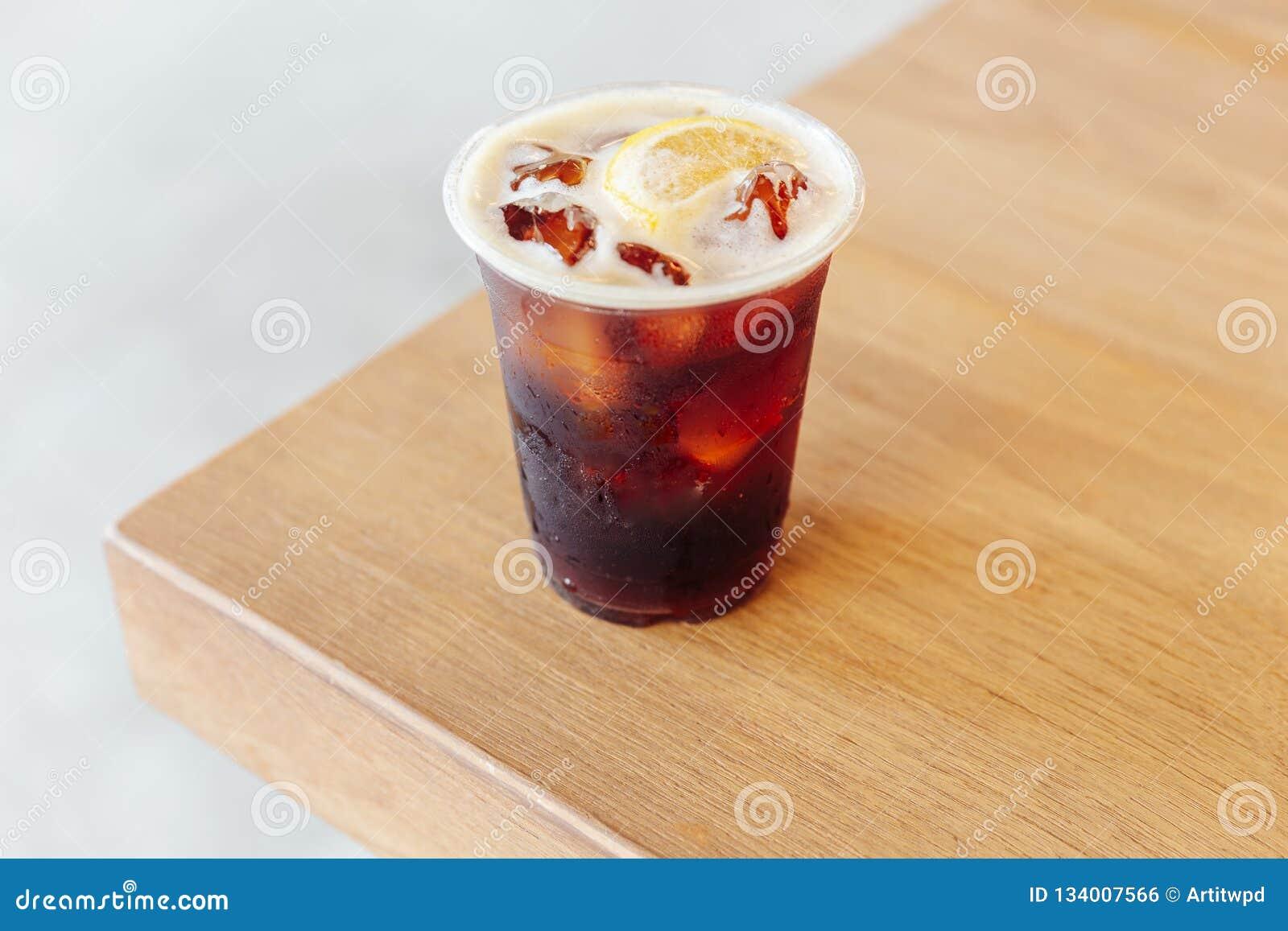 Nitro caffè freddo ghiacciato di miscela con il limone sulla tavola di legno
