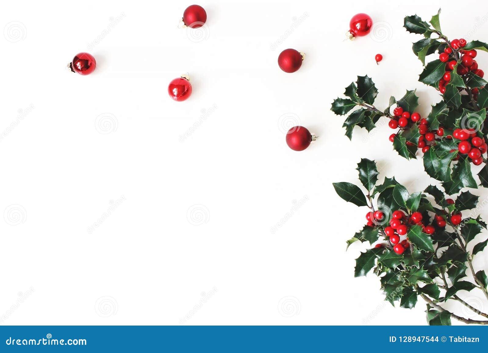 Noël a dénommé la composition, coin décoratif Boules en verre de Noël, babioles et feuilles vert-foncé d arbre de houx, rouges