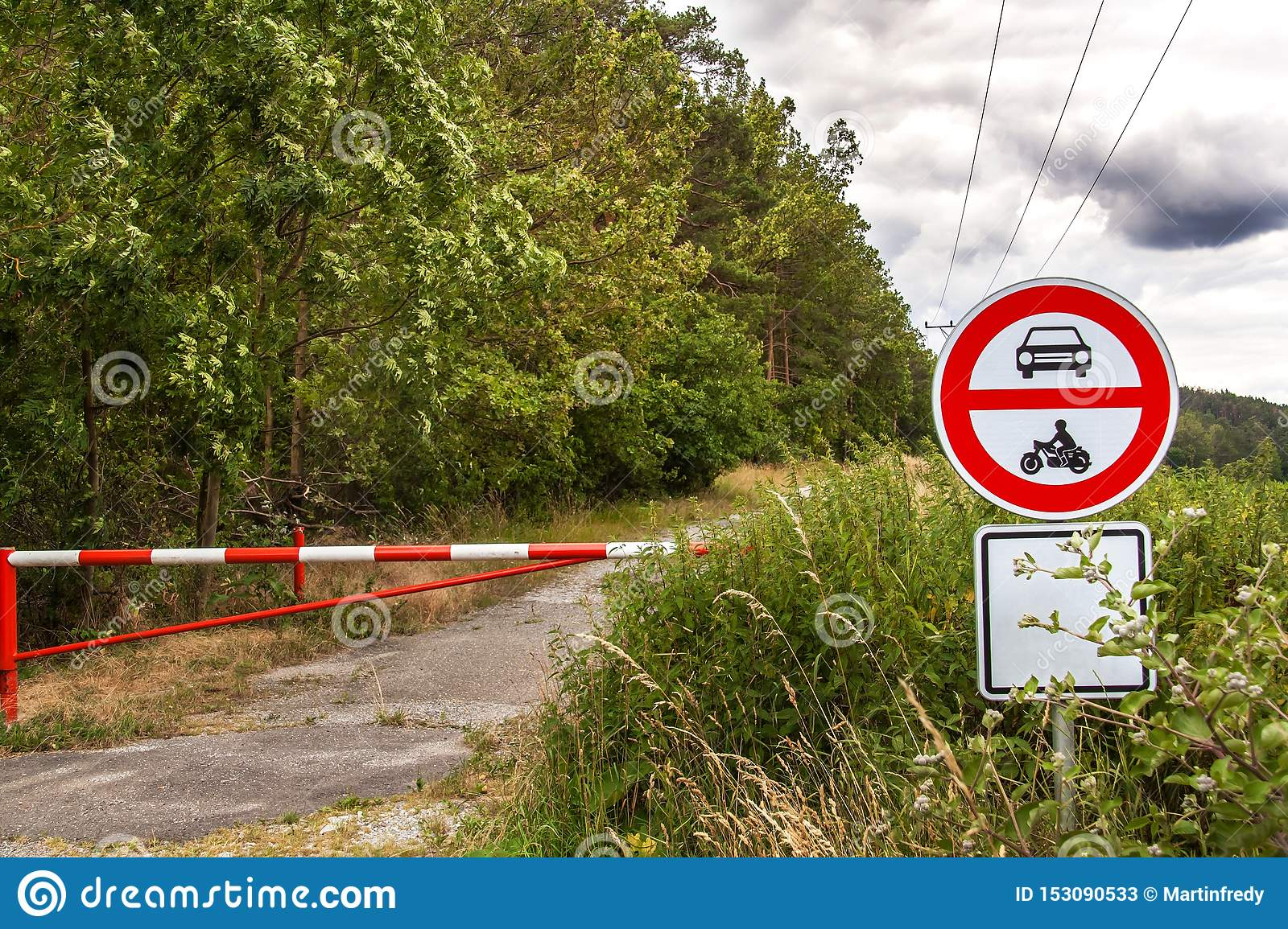No entry for motor vehicles, cycling only allowed. Storm clouds over forest road. Closed entrance to the forest. Road sign