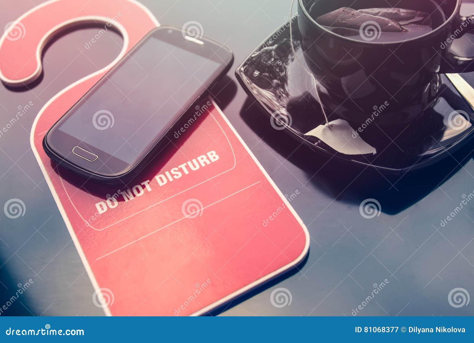 No hacen la muestra del disturbe, una taza de té y un teléfono móvil sobre fondo oscuro Hora para el concepto del resto