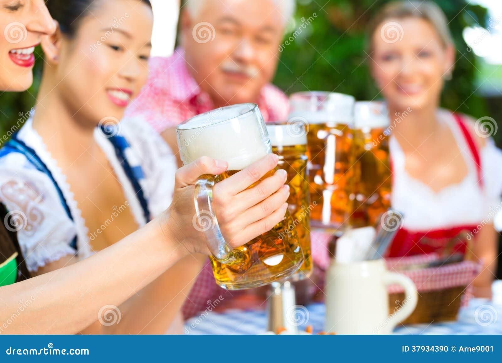 No jardim da cerveja - amigos que bebem a cerveja no bavaria