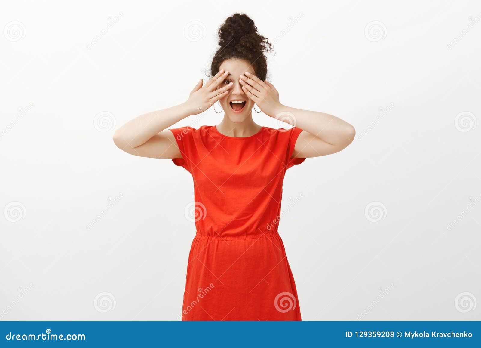 No może czekać widzieć niespodziankę Pozytywna z podnieceniem dziewczyna w eleganckiej czerwieni sukni ono uśmiecha się szeroko i