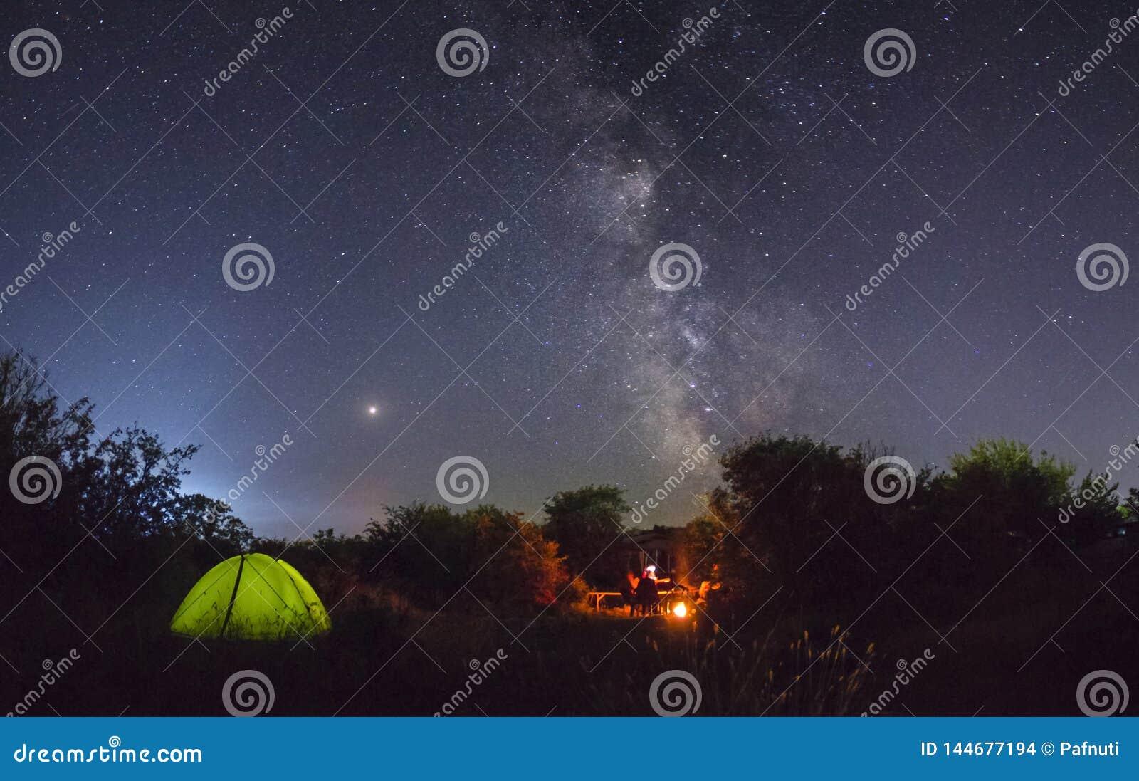 Noc camping Para turyści odpoczynek przy ognisko blisko iluminującym namiotem pod zadziwiającym nocnym niebem
