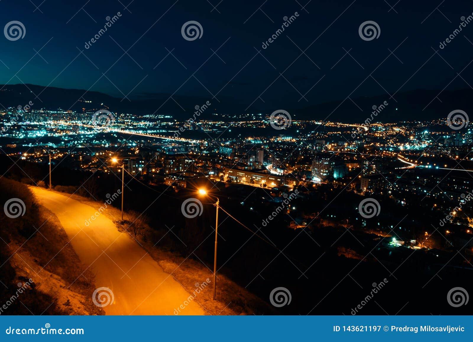 Noc widok od nadmiernego kapitału Gruzja, Tbilisi Latarnie uliczne i wzgórza otacza miasto błękitne niebo - Wizerunek