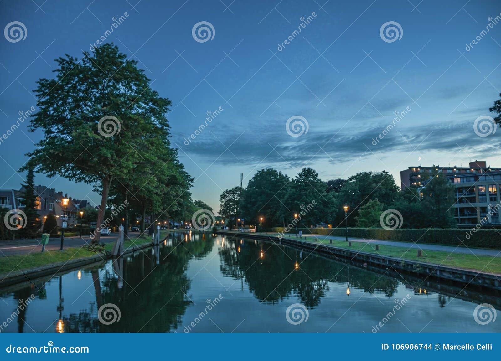 Noc widok szeroki wykładający kanał, budynki i latarni oświetlenie przy świtem w Weesp,