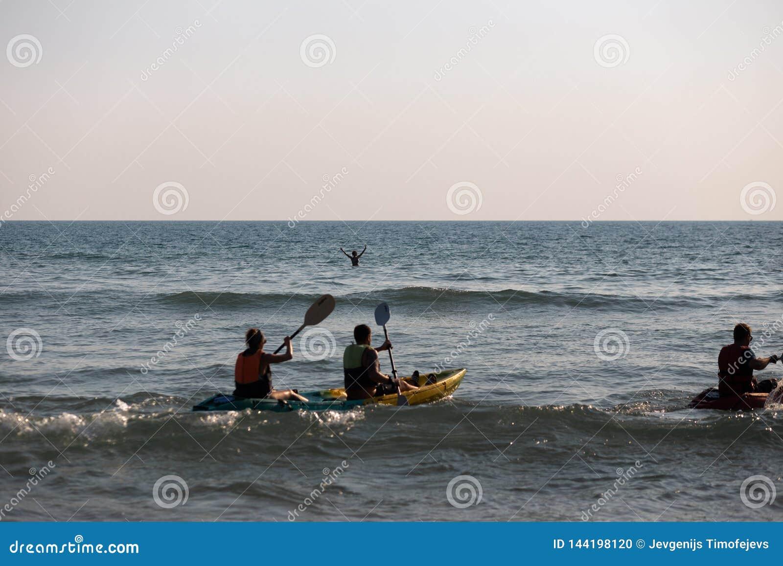 NOCAUTE CHANG, TAILÂNDIA - 9 DE ABRIL DE 2018: Homens que sweaming em um barco do caiaque - praia tropical bonita dos povos do pa