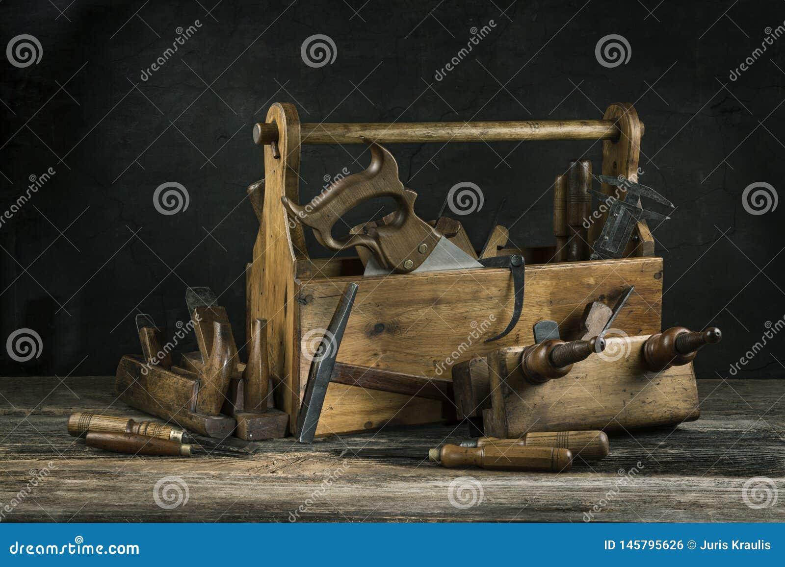 Noch lebens- alter hölzerner Weinlesewerkzeugkasten mit Hämmern, Säge, Meißeln, Fläche und Zangen in der Zimmerei