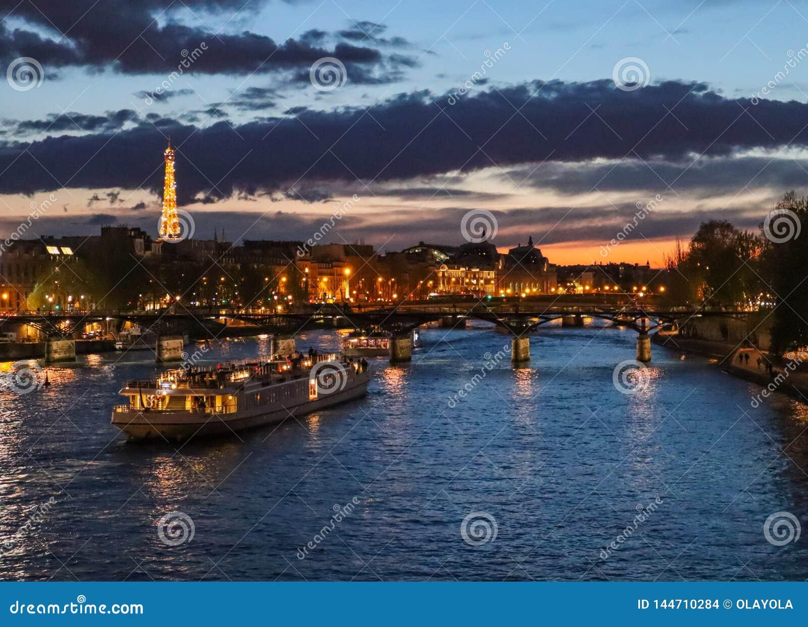 Noche hermosa Par?s, torre Eiffel chispeante, puente Pont des Arts sobre el r?o el Sena y barcos tur?sticos francia