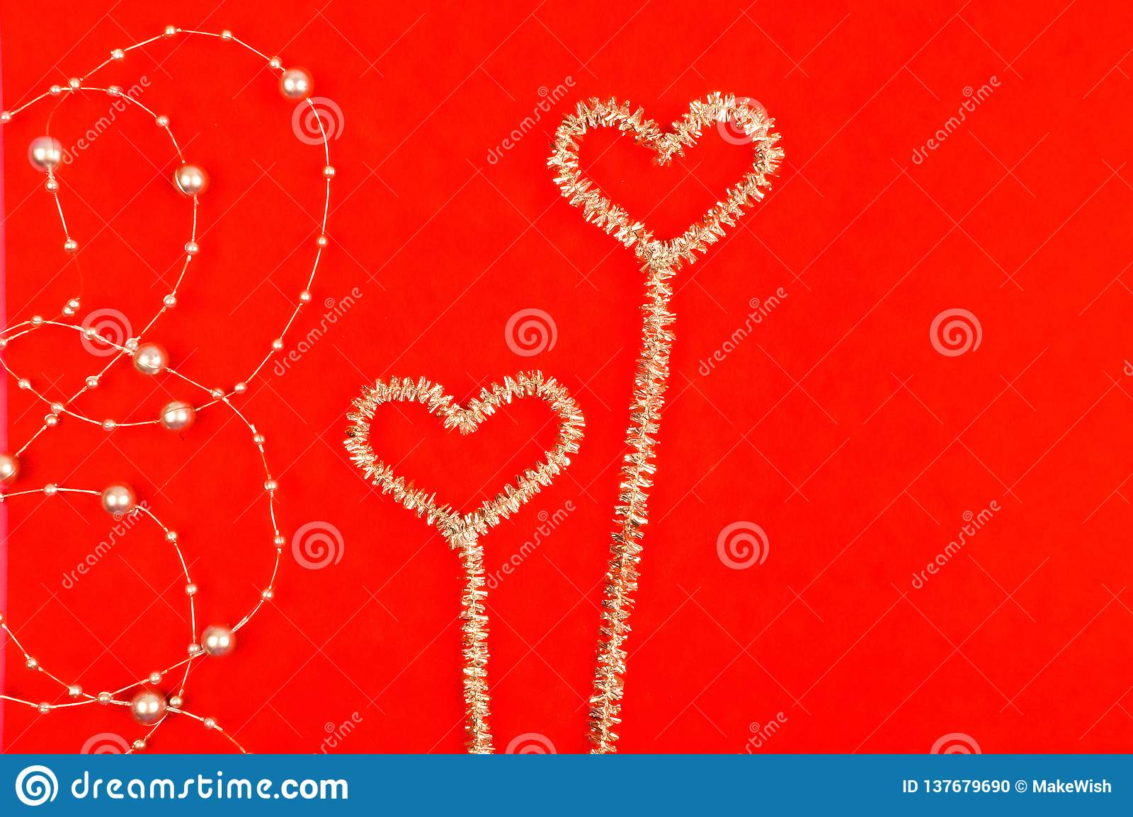 Noctilucent hearts with beads on a red background
