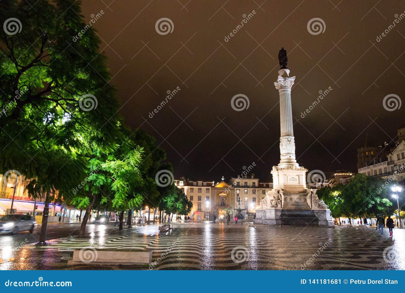 Nocy scena Rossio kwadrat i kolumna Pedro, Lisbon, Portugalia z jeden swój dekoracyjne fontanny IV