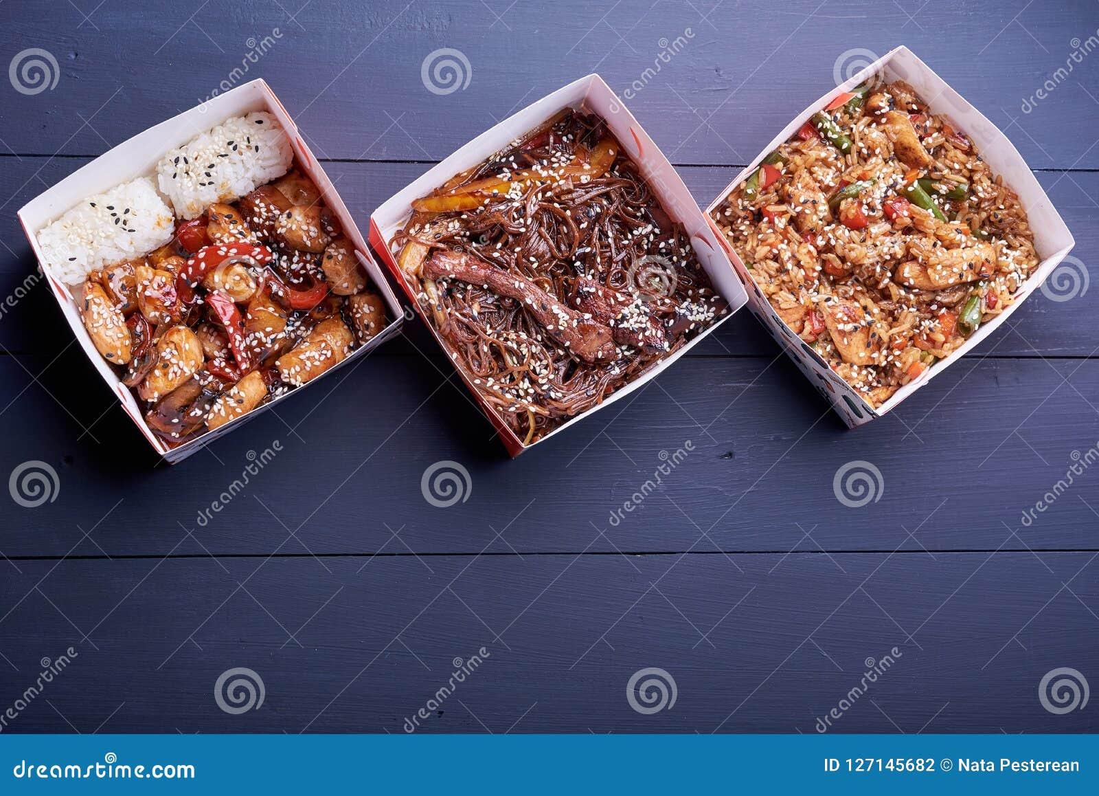 Noedels met varkensvlees en groenten in meeneemvakje op houten lijst