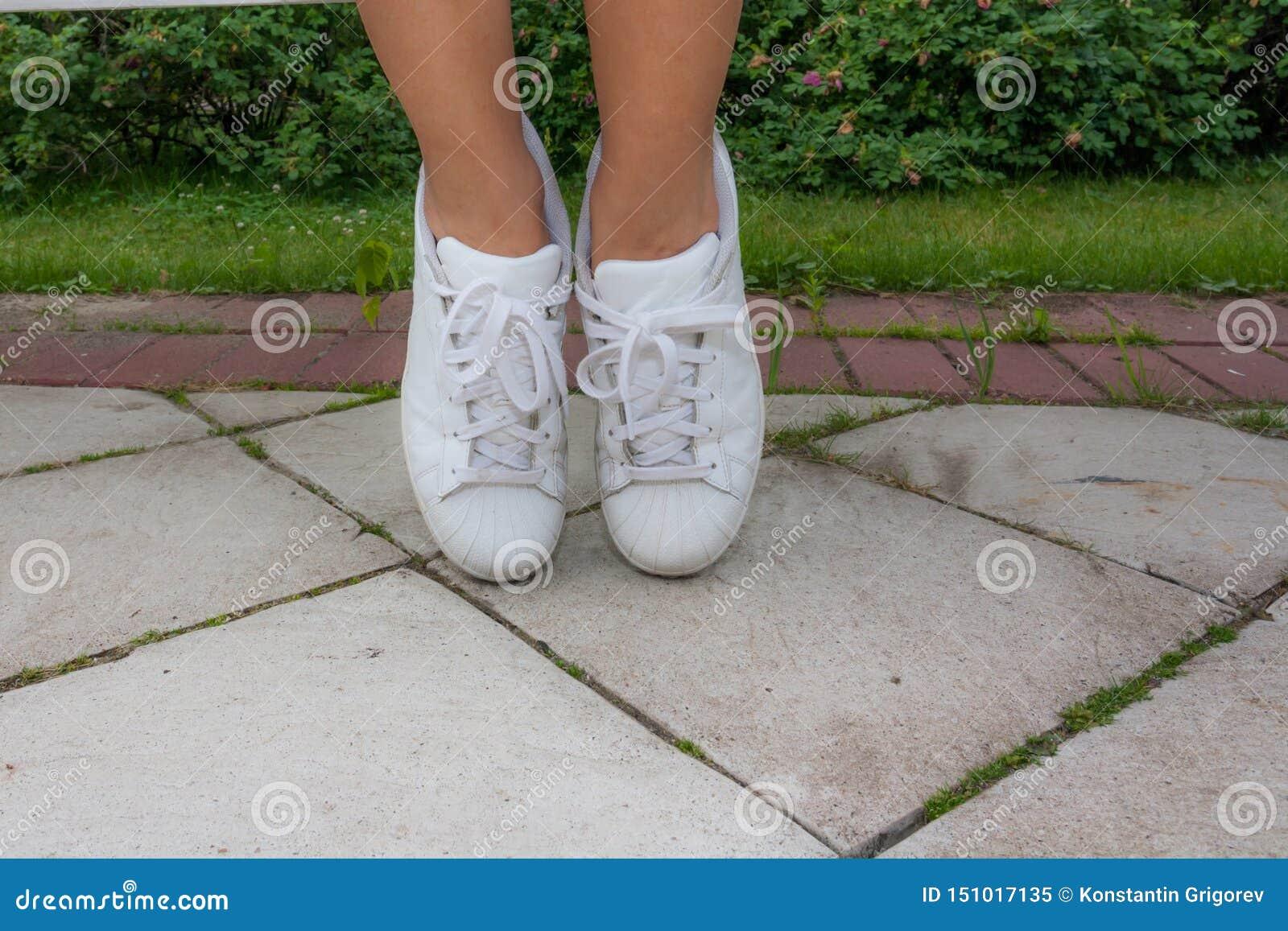 Nogi dziewczyna w białych sneakers na szarości płytce