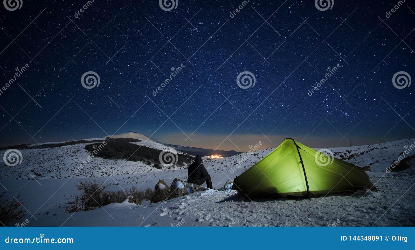 Noite estrelado no homem que olha a paisagem do inverno iluminando a barraca