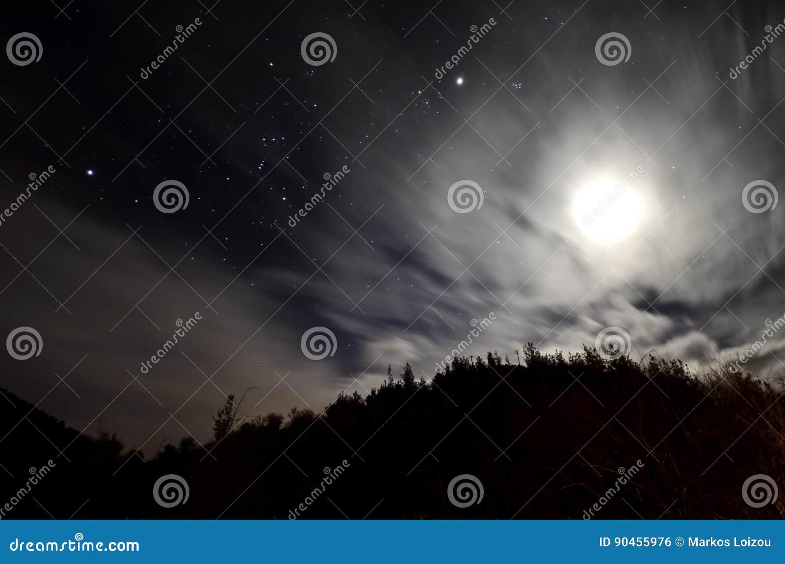 Noite nebulosa com estrelas e lua