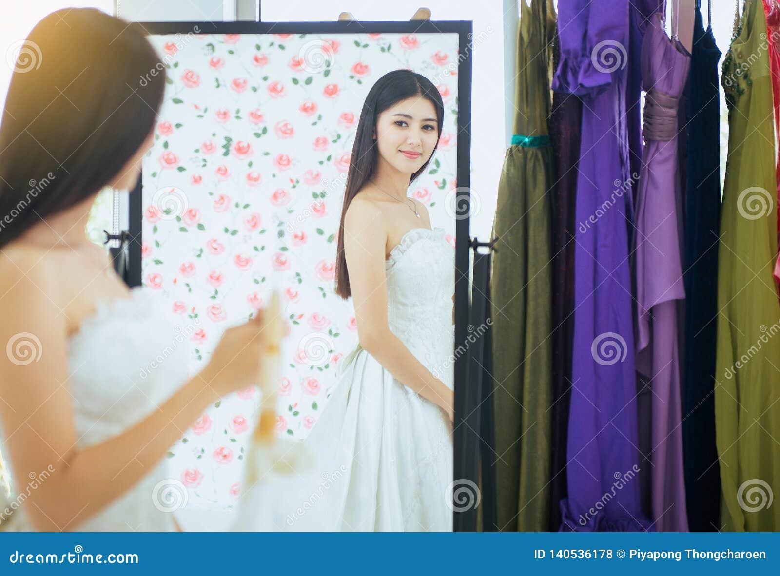 Noiva asiática nova bonita da mulher que tenta no vestido de casamento na parte dianteira do espelho, feliz e do sorriso