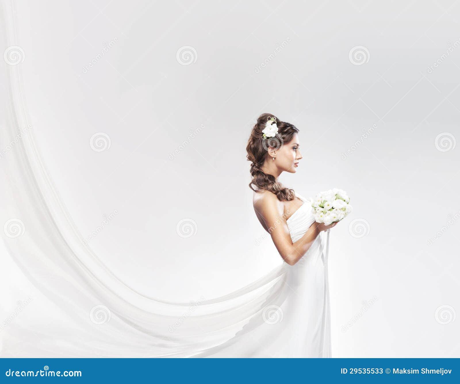 Noiva atrativa nova com o ramalhete das rosas brancas