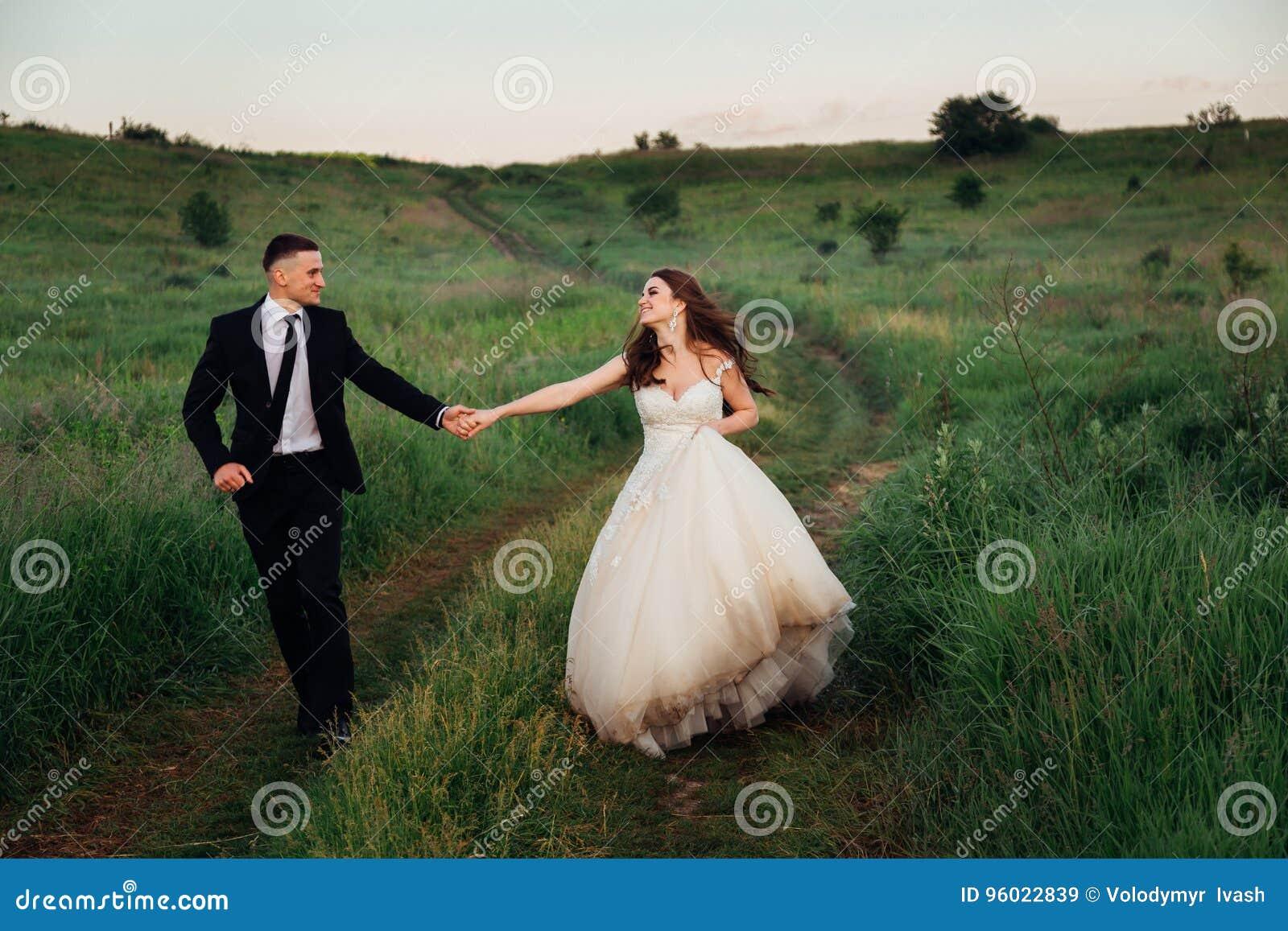 A noiva classudo aumenta o seu veste-se acima ao andar com noivo