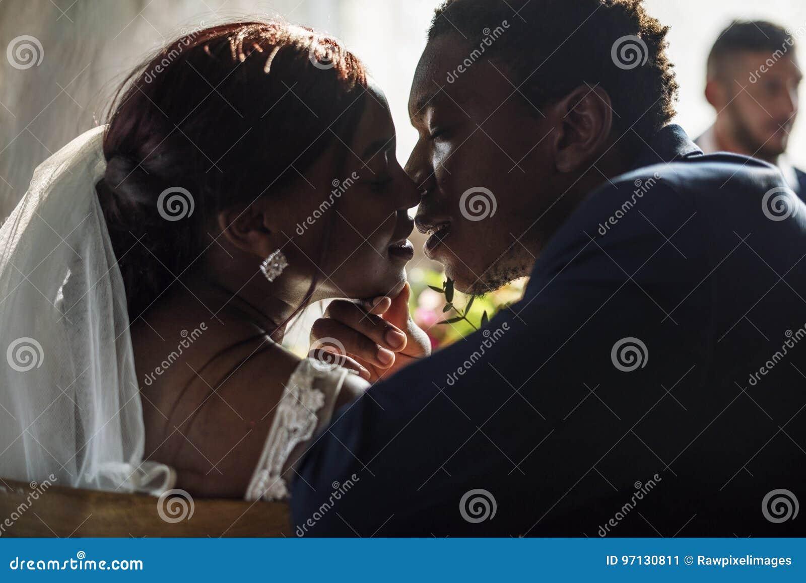 Noiva da ascendência africana do recém-casado que beija o noivo Wedding Celebration