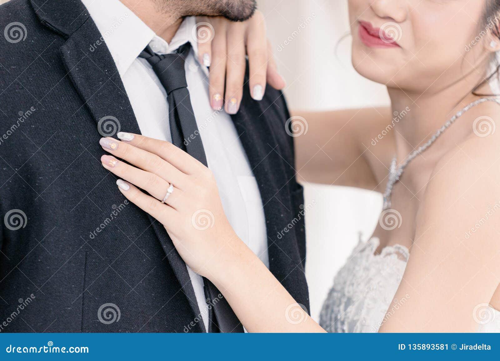 Noiva da terra arrendada do noivo com felicidade no terno do casamento
