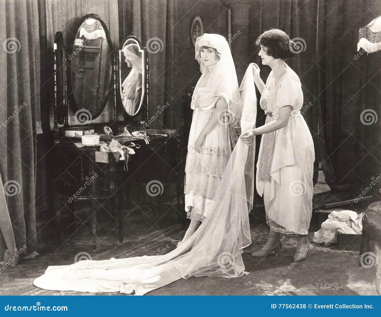 A noiva de ajuda da mulher obtém vestida