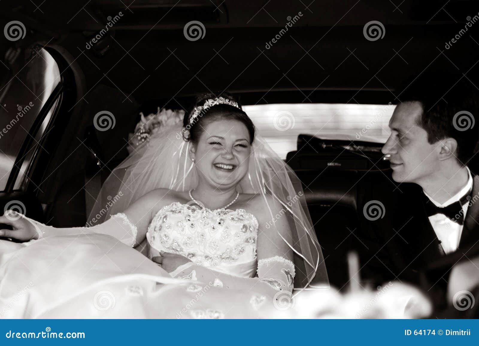 Noiva e noivo em uma limusina