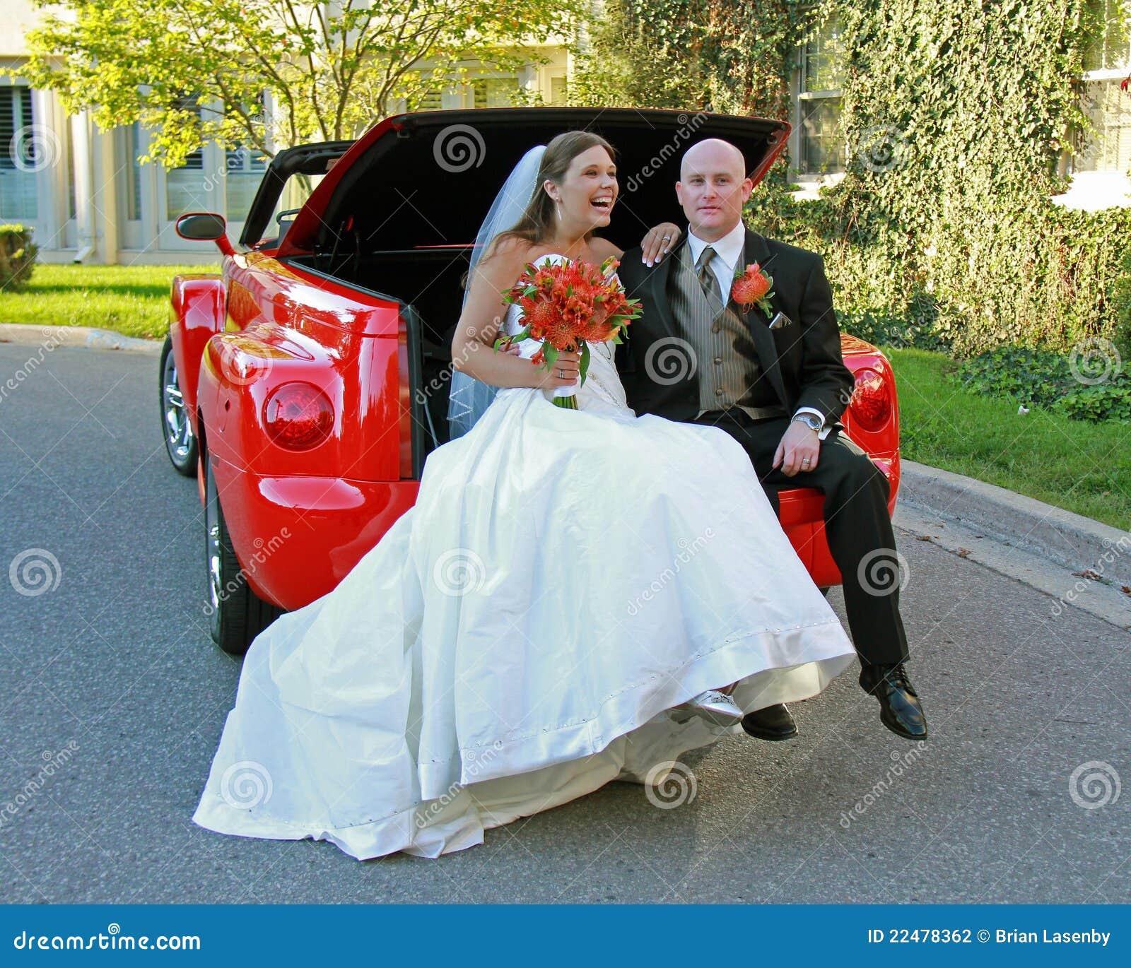 Noiva e noivo que levantam no caminhão vermelho convertível