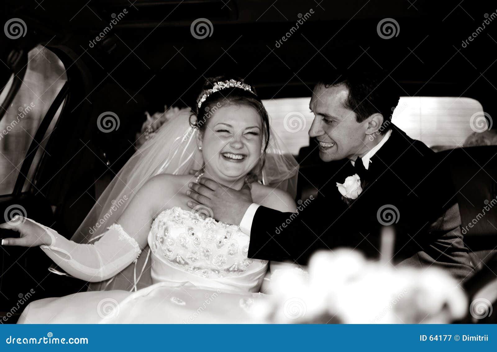 Noiva e noivo que têm o divertimento em um limo